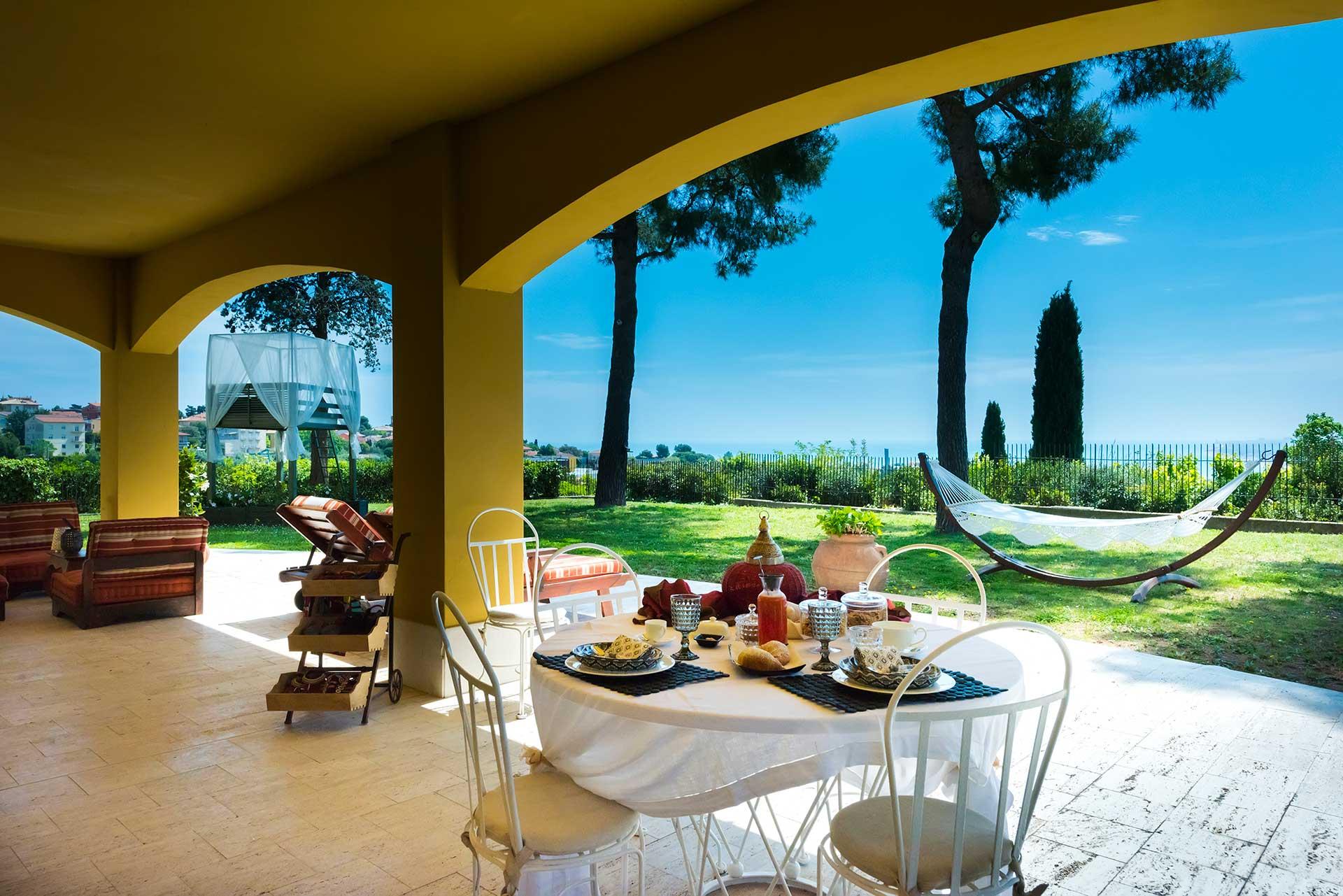 Una veduta panoramica della suite del Bed & Breakfast Tra gli Alberi e il Mare, con il suo giardino, l'amaca, lo star bed e i lettini, con una splendida vista sul mare.